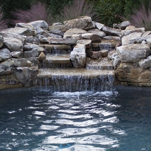 Waterfall over stacked rock  into pool